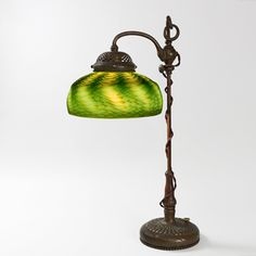 """A Tiffany Studios New York patinated bronze and Favrile glass table lamp with a green """"Damascene"""" shade with iridescent decoration suspended from standard swing am base with slide to swivel the shade and adjust its height."""