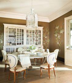 Comedor con mesa redonda y sillas tapizadas, gran alacena y paredes decoradas con motivos naturales_326236