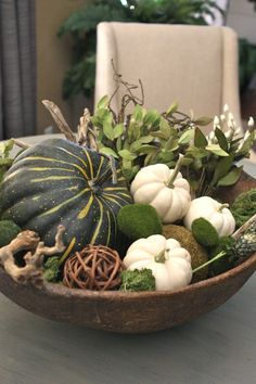 large bowl filled with fall pumpkins and greenery