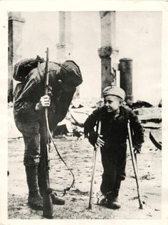 1944-Russian boy whose parents were taken away by the retreating Germans, talks to Red Army soldier. Germans forced residents of his village to leave their homes and his feet are now frostbitten.