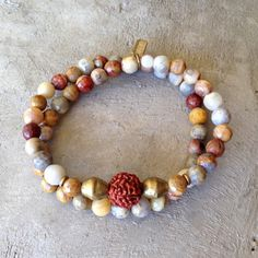 54 bead mala convertible Bracelet Or Necklace, made with crazy agate and red Jasper, for healing and grounding, with an Om pendant. It wraps as a bracelet, (stringed on thick hi-tec elastic) and may be worn as a mid-length necklace. Cool unisex style!