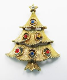 Lovely vintage gold toned Christmas tree pin containing multi colored round rhinestones. Pin measures 2 inches x 1 inch. Signed J.J. (Jonette Jewelry Co.) and manufactured during the 1950s, this piece is in excellent condition with no chipped, missing or damaged stones. For more Vintage and Antique costume jewelry and collectibles, visit us at www.gildedtrifles.com.