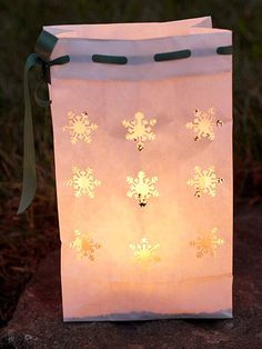 Light up a walkway with a snowflake motif luminaria. Use a snowflake paper punch to create the designs on a paper bag. Punch holes in the top edge of the bag and weave ribbon through the holes. Fill the bags with sand or aquarium rocks for weight. Add a candle and watch the light shine through the design.