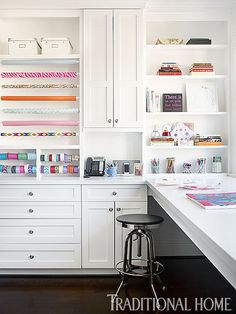 Fabulous gift wrapping room boasts shelf filled with white boxes over stacked tension rods adorned with various wrapping paper  and ribbons situated over built-in drawers beside white shaker cabinets topped with white quartz.