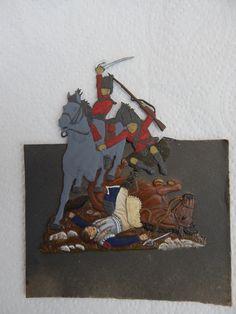 Une partie du plat d'étain a été mise en peinture : La cavalier français au sol et son cheval.