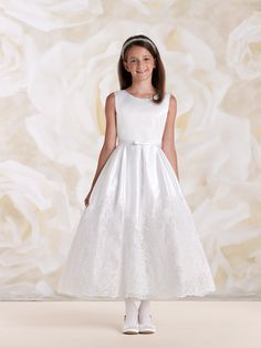 Sleeveless satin, tulle and lace tea-length A-line dress with jewel neckline, satin bodice features a thin waistband with center front bow and covered buttons down back, box pleated skirt accented with wide illusion lace band at hem, perfect as a flower girl dress or First Communion dress. Sizes: 2 – 14