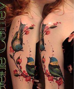 Motive mit Blumen und Vögeln am Oberarm