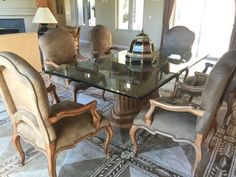 ELEGANT KREISS COLLECTION DINING ROOM SET CONSISTING OF 6 UPHOLSTERED ARM CHAIRS AND TABLE. THE BEVELED GLASS TOP TABLE MEASURES 29H X 90L X 48W. IT SITS ON AN OVAL SHAPED INVERTED RIBBED BASE. THE CHAIRS HAVE TAUPE COLORED UPHOLSTERY WITH NAIL HEAD TRIM. THEY MEASURE 43H X 24W. SET SHOWS WEAR, CONSISTENT WITH USE, AND SOME STAINING ON THE UPHOLSTERY.