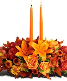Autumn Gathering Centerpiece  What a welcome for your Thanksgiving dinner guests – a magnificent centerpiece featuring lilies, roses and soft candlelight. They'll be complimenting you all through the meal.    The glorious autumn arrangement includes orange Asiatic lilies, orange alstroemeria, rust cushion spray chrysanthemums, orange roses, yellow cushion spray chrysanthemums and bronze button spray chrysanthemums accented with fresh greenery.