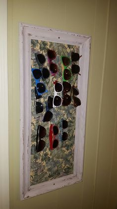 I made this! Just cover a board to fit your frame, cover back board with chicken wire, wrapping around edge and staple it to the board. Fit board back into frame and secure with tiny nails angled onto back to secure board. I screwed finished piece into wall to hold in place. LOVE my sunglass collection!
