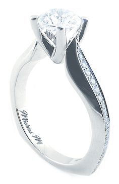 A modern twist on a classic design. Uniquely curving shoulders and flowing channel set diamonds lead to a stunning solitaire center-stone on this Michael M Engagement Ring