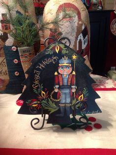 Nutcracker on a Christmas tree plate, painted with a Jo Sonja design.