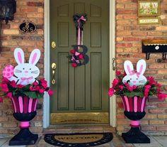 Linda entrada con 2 floreros pintados y decorados con conejos y flores...En la puerta una corona pequeña para no opacar a los conejos.