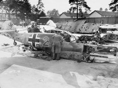 Civilian staff investigate the fuselage of a Messerschmitt Bf 109E4, 'Red 2', of 3./LG 2, in the grounds of a technical college, 1940. Note the 'Mickey Mouse' staffel emblem on the rear fuselage.