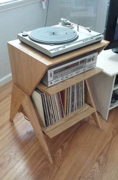 This Solid Ash Wood Record Player Stand is built to order by BLR Woodworking (BLR Woodworks on Etsy) in Los Angeles. It is made from solid hardwoods and is constructed using classic wood joinery techniques. Inspired by 1950s Atomic Style furniture, this record player stand has room for 1 turntable, 1 receiver, and approximately 75 records. The shelves measure 19 wide x 17 deep. The receiver opening measures 6 7/8 high, and the record compartment measures 14 high. Overall dimensions: 30 1...