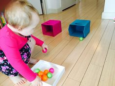 Rolling ping pong balls into boxes, toddler activities, activities for one year old, activities for two year old, fun activities for toddlers, indoor activities for toddlers, rainy day toddler activities, activities for 20 month old, things to do with toddler, educational activities for toddlers, learning activities for toddlers