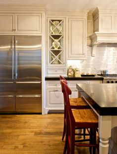 brushed aluminum backsplash, white cabinetry, black granite counters. sleek.