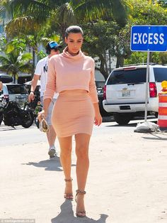 Pretty in peach: Her high-necked dress clung to Kim's curves