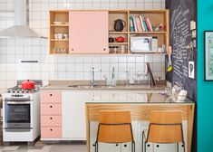 This kitchen features pinewood cabinets with white and pink doorways, as well a blackboard that covers one wall. There is also a small open pantry that is painted turquoise.