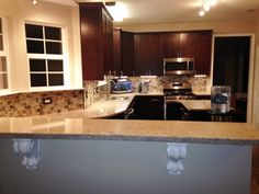Kitchen Remodel- Silestone Bar top, White Corbels, Stainless Steel Appliances, Wood Cabinets