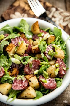 Chorizo And Roasted Potato Salad - Spicy sausage and crispy roasted potatoes, all in a homemade dressing over a bed of greens. #Paleo