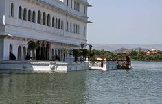 Staff of the Lake Palace hotel in Udaipur, located in the middle of Lake Pichola. They are at the waiting location, just outside the lobby, where guests arrive on boat and are ceremoniously welcomed. In the background can be seen the domes of the Oberoi Udaivilas.