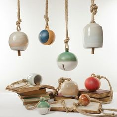 Ceramic Bells – Michele Quan, built by hand and finished with refined glazes. They are suspended from a thick earthy hemp rope and some designs have a knocker made of reclaimed wood.