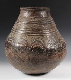 AFRICAN POTTERY - Mandinka People, Guinea, Large Honey Pot with ovoid base, tapered top with rolled rim, raised geometric decoration, in glazed umber clay.
