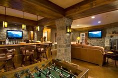 rustic basement (totally great for guys :) with bar, foosball table, fireplace, & TVs
