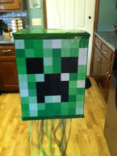 """Creeper pinata--made from a diaper box, spray painted green, with a creeper face google image printed on photo paper and taped on. Filled this with TNT (baggies of Pop-its) since you get TNT from a creeper. Used the TNT to defeat """"King of the Pigmen"""" in the Netherworld to get back the stolen treasure. """"King of the Pigmen"""" was just a poster drawn by my talented hubby."""