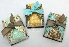 """Wrap two Hershey Nuggets with a strip of 1"""" x 3"""" Very Vanilla Card Stock stamped with the It's a Wrap Holidays """"Give Thanks"""" stamp.  Punch two Scallop Circles out of Spice Cake Designer Paper and adhere them to the inside of a piece of 1 3/8"""" x 2"""" Soft Suede Card Stock  with SNAIL Adhesive.  Set the nuggets inside, wrapping the scallop circles around the nuggets and tie with a ribbon to hold them in place."""