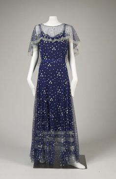 Circa 1935 Evening ensemble (dress, belt, capelet, and slip) by Gabrielle Chanel. Silk Ankle length bias cut evening dress  with shoulder straps in royal blue silk bobbin net or tulle, machine-embroidered with scattered star pattern and attached underdress of blue silk crepe with alternating bands of blue and white net at the hemline.