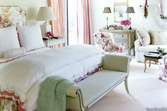 """""""When you're the parents of six children, you absolutely need a retreat,"""" designer Susan Zises Green says, and the Connecticut master bedroom, with its pinks and green and roses everywhere, its comfortable sitting area, its deft touches of sophisticated gilt, nicely fits the bill. The Harlow bench is from John Rosselli. A few of the client's favorite shell-encrusted boxes from her collection are clustered on the custome green dresser. - HouseBeautiful.com"""