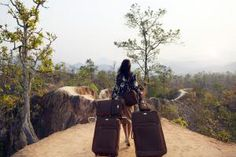 Woman walking on dirt road with suit cases, rear view. Pai Canyon, Thailand. - Freudenthal Verhagen/Stone/Getty Images