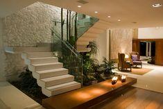 Jardim de Inverno sob escada moderna ocupando o espaço livre e embelezando o ambiente