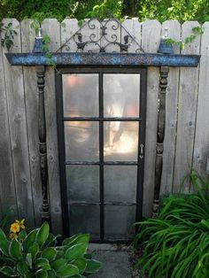 """Garden Salvage  I took an old door and coated the glass with mirror paint, then I mounted it on my fence. I added some porch poles and bunk bed slats as a frame around the door; decorating it with paint and flower pot finials. I added a decorative piece of steel as a topper and put some stepping stones in front of it. This is my """"secret"""" door to nowhere."""