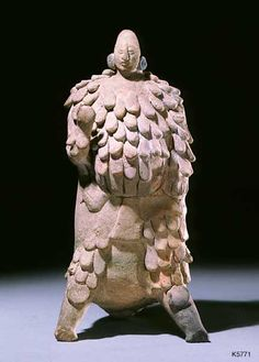 Jaina. clay height 23.5 cm. Standing figure in feather costume. The small head suggests the figure originally wore a hat or helmet. The back leg of the tripod ends in a whistle.