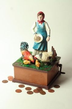 Chicken Feed Crank Bank     The farmer's wife scatters a coin from the seed plate while the poultry peck and pivot. Hand painted cast iron. Plays Old Macdonald Had a Farm.