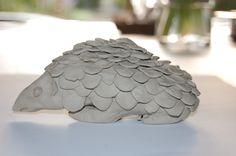 Opdracht 2: Op het werk in klei is een schubben textuur op te merken. De schubben overlappen elkaar gedeeltelijk aan het oppervlak.