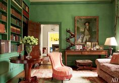 Light salmon pink armless chair and couch are paired with green walls and rustic wooden furnishings.