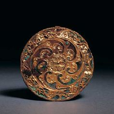 Bronze and gold circular plaque, China, Eastern Han dynasty, 25 – 220 AD, Diameter: 2 inches, 5 cm.  A circular ornament consisting of a thin bronze disc overlaid with openwork gold sheet, which is cut into a pattern formed by seven shaped petals radiating around a central stylised flower head. The seven petals are inlaid with tiny gold granular work, and with small turquoise and coral beads set in gold cloisons.
