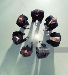 Stock Photo : Group of business people in circle using mobile phones, overhead view