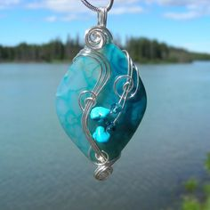 For more information about my craft, please visit my profile page.   UNDER THE SEA is a 125 carat handcrafted wire wrapped blue dragon vein agate pendant that I created swirling and shaping non-tarnish sterling silver plate wire by hand, adding turquoise chips and Swarovski crystals to enhance the natural beauty and shape of the stone. The unique pattern in this glass-like gemstone creates a deep 3-dimensional effect with a brilliant turquoise color. The combination of the elegant, swirly…