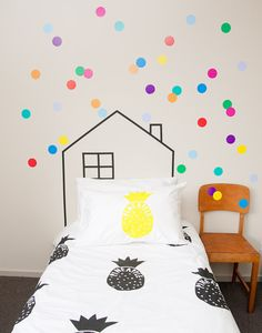 polka dot wall stickers and playhouse outline in washi tape at the head of the bed - cute for a kid's room