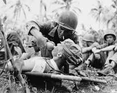 Marine give drink of water to injured comrade