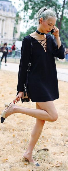 Soo Joo Park stops to fix her shoe in a black lace-up vamp dress and a blue ponytail