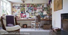 Alle Gedanken und Ideen gesammelt an einem Ort: Ein Moodboard als Wanddeko vereint das Nützliche mit dem Dekorativen. So kann man sich bei der Arbeit an dem langen Holztisch immer wieder inspirieren lassen. Für die nötige Entspannung sorgt ein Rattansessel vor dem Kamin.