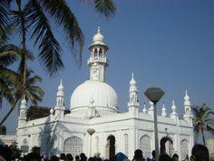 The Haji Ali Dargah is a mosque and dargah located on an islet off the coast of Worli in Mumbai. The revered dargah is located on a bed of rock 500 yards into the Arabian Sea. The B. Haji Ali Dargah, Muslim Religion, Jama Masjid, Coach Tours, Mughal Architecture, Arabian Sea, Rose Wallpaper, In Mumbai, Pilgrimage