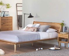 Scandinavian Designs - The Nordic-inspired Bolig bed is crafted from solid poplar and features a warm stain exposing the natural texture of the wood. The platform style and tapered legs add a mid-century modern feel.