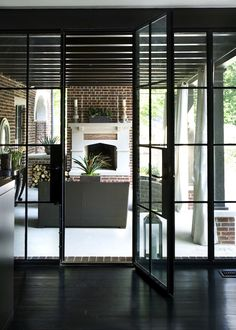Stunning dark stained hardwood floors with black metal French doors leading to outdoor covered patio area.